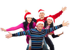 Excited Christmas friends with hands up. Excited group of friends wearing colorful clothes and Santa hats and standing with  hands in the air laughing isolated Stock Image