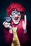 Excited Clown With Camera At Kids Birthday Party. Excited Young Male Photographer Clown Holding Camera While Shouting Out Cheese At A Kids Birthday Party Stock Image