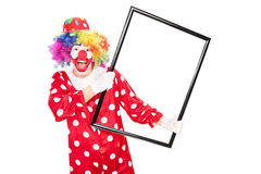Excited clown holding a big picture frame Royalty Free Stock Image