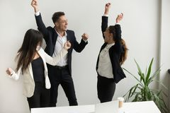 Excited colleagues celebrating online win raising hands. Excited colleagues dancing in office throwing hands up celebrating company online win, happy for victory Stock Photos