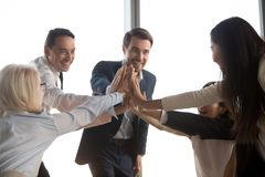 Excited colleagues give high five motivated for success. Excited diverse colleagues give high five engaged in teamwork at office briefing motivated for success stock photos