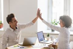 Excited colleagues giving high five after successful deal closin. Excited diverse millennial colleagues giving high five after closing successful deal online at royalty free stock photos