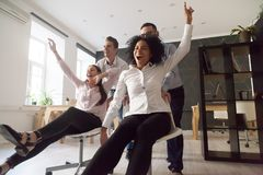 Excited colleagues having fun riding chairs during work break. Excited multiracial workers having fun during work break in office, diverse colleagues riding royalty free stock photos