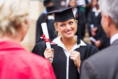 Excited college graduate. Excited female college graduate looking at parents Royalty Free Stock Photos