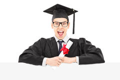 Excited college graduate holding diploma and standing behind bla Stock Image