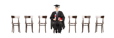 Excited college student holding diploma, seated on wooden chair. Excited college student holding diploma and looking at camera seated on wooden chair isolated on Stock Image
