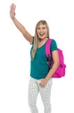 Excited college student waving her hand. Excited blonde college student with backpack waving her hand to her friends Royalty Free Stock Images