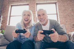 Excited concentrated middle-aged couple sitting on a couch in th royalty free stock image