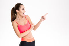 Excited content pretty fitness girl in sportwear pointing away Royalty Free Stock Photography