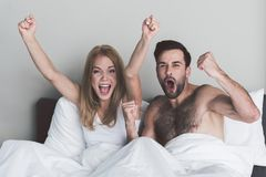 Excited couple celebrating victory of their team in bedroom Royalty Free Stock Photography