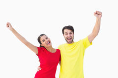 Excited couple cheering in red and yellow tshirts Royalty Free Stock Images