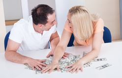 Excited couple collecting money Stock Photos