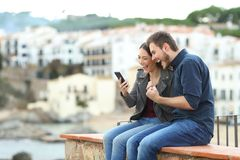 Excited couple finding news on phone on a ledge. Excited couple finding news on smart phone on a ledge with a town in the background stock photography