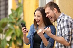 Free Excited Couple Finding Online Offers On Phone In The Street Stock Images - 142297764