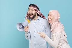 Excited couple friends arabian muslim man wonam in keffiyeh kafiya ring igal agal hijab clothes isolated on blue