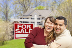 Excited Couple in Front of For Sale Sign and House Royalty Free Stock Images