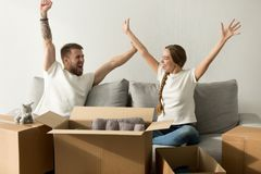 Excited couple glad to move into new home celebrating together. Excited men and women glad to move in new home, happy house owners raising hands celebrating stock photo
