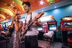 Excited couple holding gaming guitars in hand having fun. Couple playing the guitar game holding gaming guitars at a gaming parlour. Smiling men and women having stock images