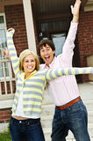Excited couple at home. Young excited couple celebrating in front of home Stock Photos