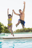 Excited couple jumping into swimming pool on holidays Royalty Free Stock Photo