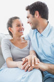 Excited couple looking at each other on the couch Stock Photo