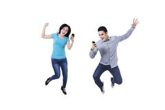 Excited couple with mobile phone. Excited young couple jumping with mobile phone Royalty Free Stock Photos