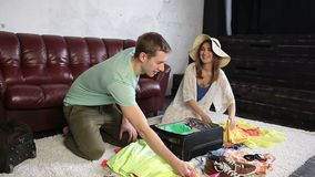 Excited couple packing traveler case for vacation stock footage