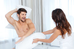 Excited couple pillow fighting at home Royalty Free Stock Image
