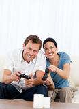 Excited couple playing video games together. On the sofa at home Royalty Free Stock Images