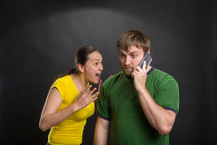 Excited couple playing wth a mobile phone Stock Photos