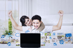 Excited couple raised arms looking at laptop Stock Images