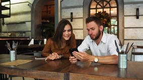 Excited couple reading e-mail with good news in a smartwatch in a coffee shop with a window in the background with a