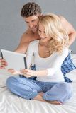 Excited couple reading a tablet computer Stock Image