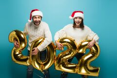 Excited couple in santa hats holding golden balloons in shape of 2022. On blue,stock image