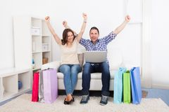Excited couple with shopping bag. Excited Young Couple Sitting On Couch With Shopping Bag Royalty Free Stock Images