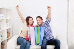 Excited Couple With Shopping Bag. Excited Young Couple Sitting On Couch With Shopping Bag Royalty Free Stock Image