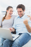 Excited couple sitting on the couch using laptop together Royalty Free Stock Photography