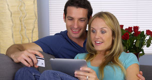 Excited couple using credit card with tablet. At home Royalty Free Stock Photo