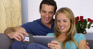 Excited couple using credit card with tablet Stock Images