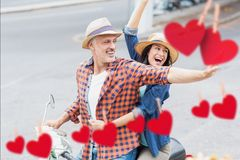 Excited couple waving hands while riding scooter Royalty Free Stock Photography