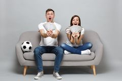 Excited couple woman man football fans cheer up support favorite team, holding fan of money in dollar banknotes, cash stock photos