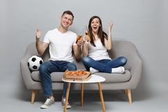 Excited couple woman man football fans cheer up support favorite team with soccer ball, holding beer bottles isolated on. Excited couple women men football fans stock image