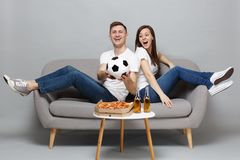 Excited couple woman man football fans cheer up support favorite team with soccer ball, sitting back to back isolated on. Excited couple women men football fans royalty free stock photography
