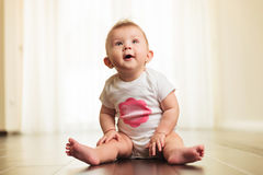 Excited and curious little baby girl looks up. To side while sitting on wooden floor Royalty Free Stock Photos