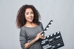 Female holding movie clapper board. Excited curly female holding movie clapper board, slate film Royalty Free Stock Photos