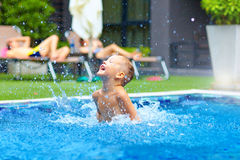 Excited cute boy having fun in pool Royalty Free Stock Photos