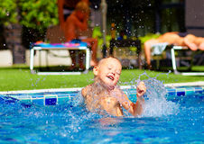 Excited cute boy having fun in pool Royalty Free Stock Image