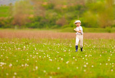 Excited cute boy running blooming field, spring countryside Stock Photos