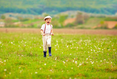 Excited cute boy running blooming field, spring countryside Stock Image