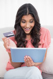 Excited cute brunette sitting on couch holding credit card and tablet Royalty Free Stock Photo